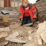 Karen Ladniuk (Richard III Society) cleaning a path made from re-used medieval tiles (Credit - University of Leicester)